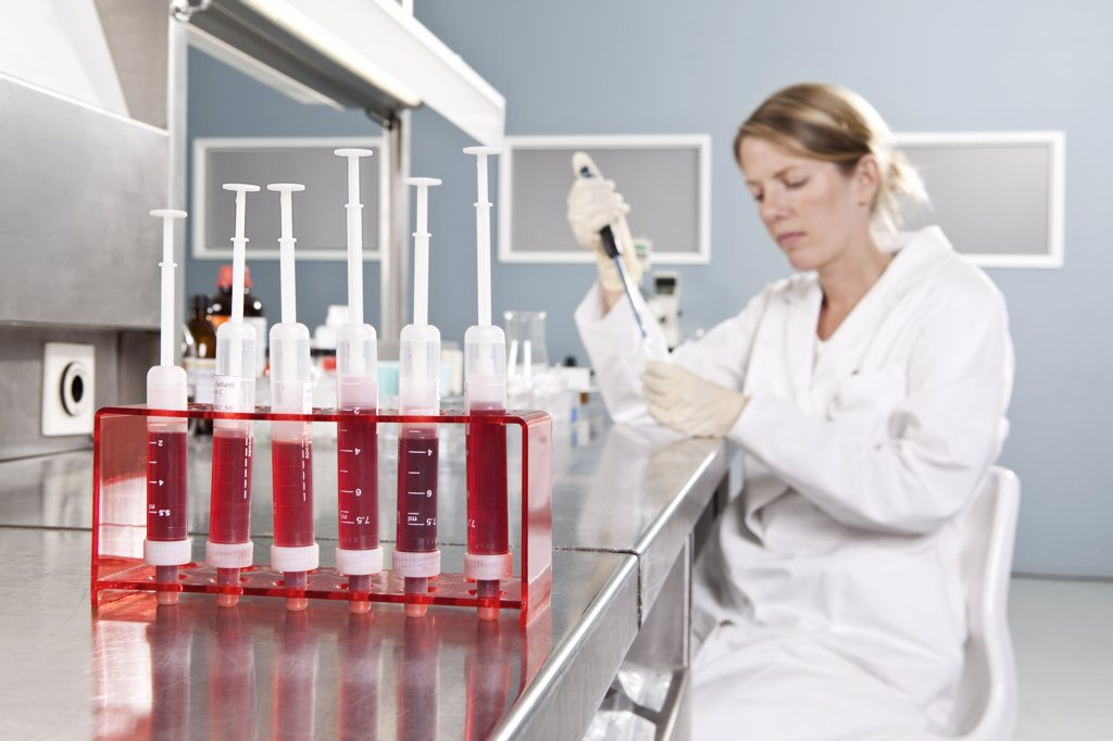 A row of vials holding blood and a lab technician working in background, focus on foreground : Stock Photo