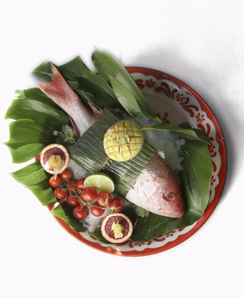 Red snapper wrapped in a banana leaf with garnish : Stock Photo