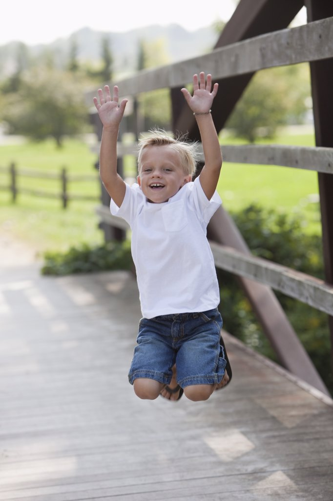 Boy jumping on bridge : Stock Photo