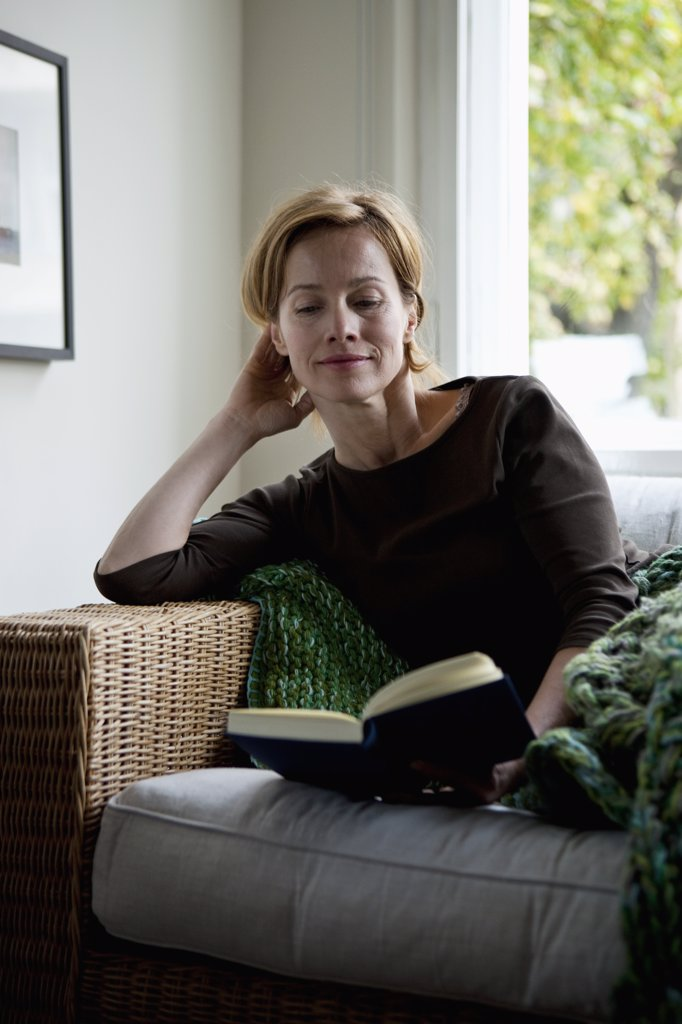 A woman reading a book while reclining on a sofa : Stock Photo