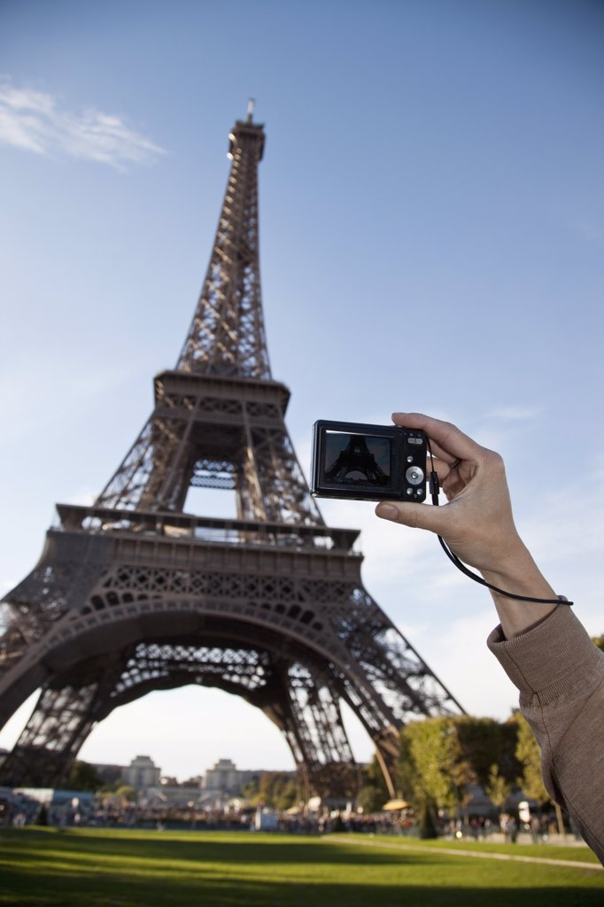 A woman photographing the Eiffel Tower, focus on hand : Stock Photo