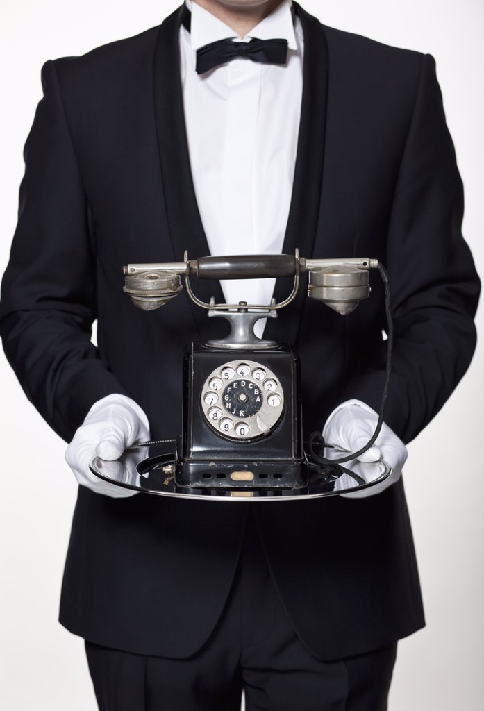 A butler holding an antique rotary phone on a silver tray, midsection : Stock Photo