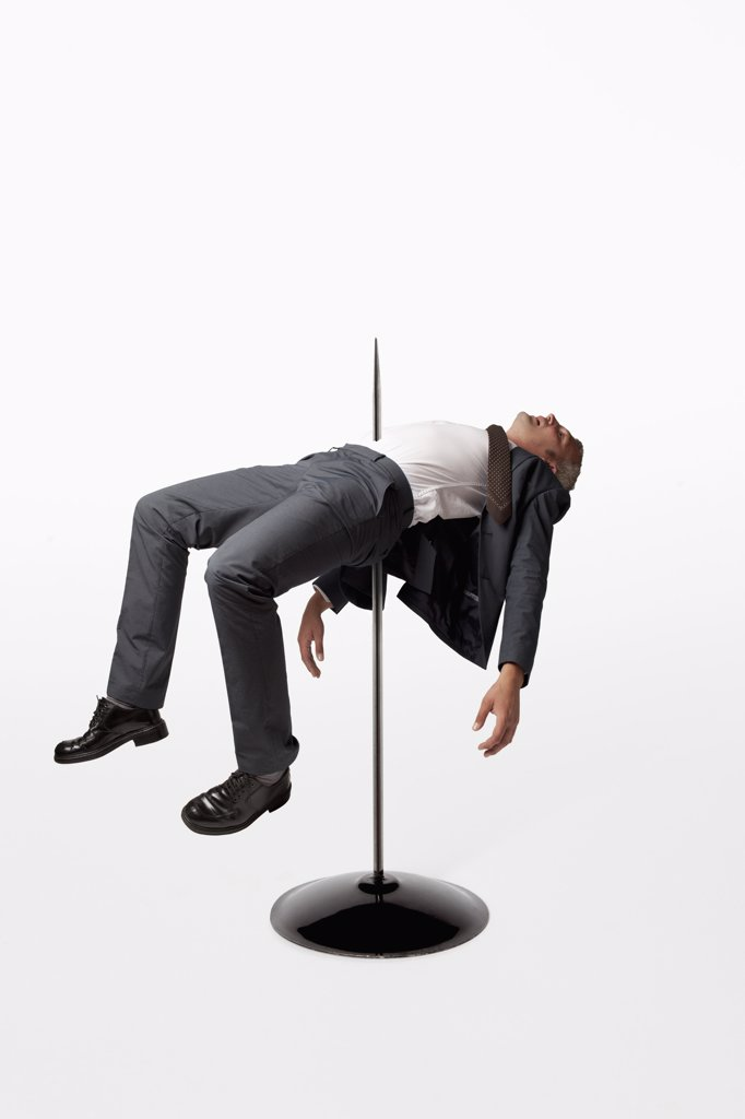 A businessman impaled on a spindle : Stock Photo