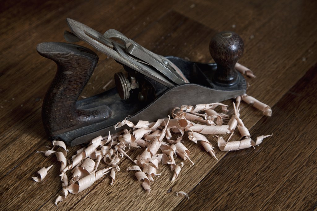 A wood planing tool and shavings : Stock Photo