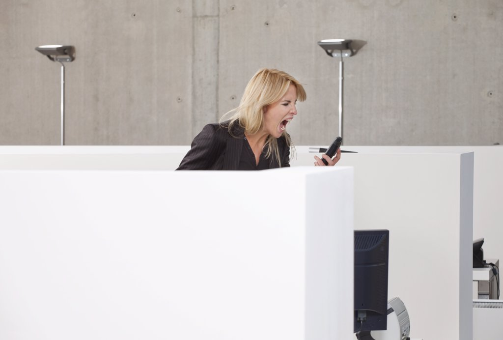A woman screaming into a mobile phone in an office cubicle : Stock Photo