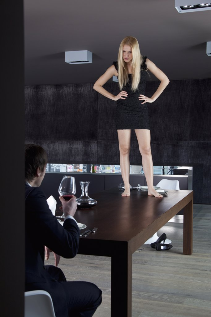 Girlfriend stands on dinner table displeased with her boyfriend. : Stock Photo