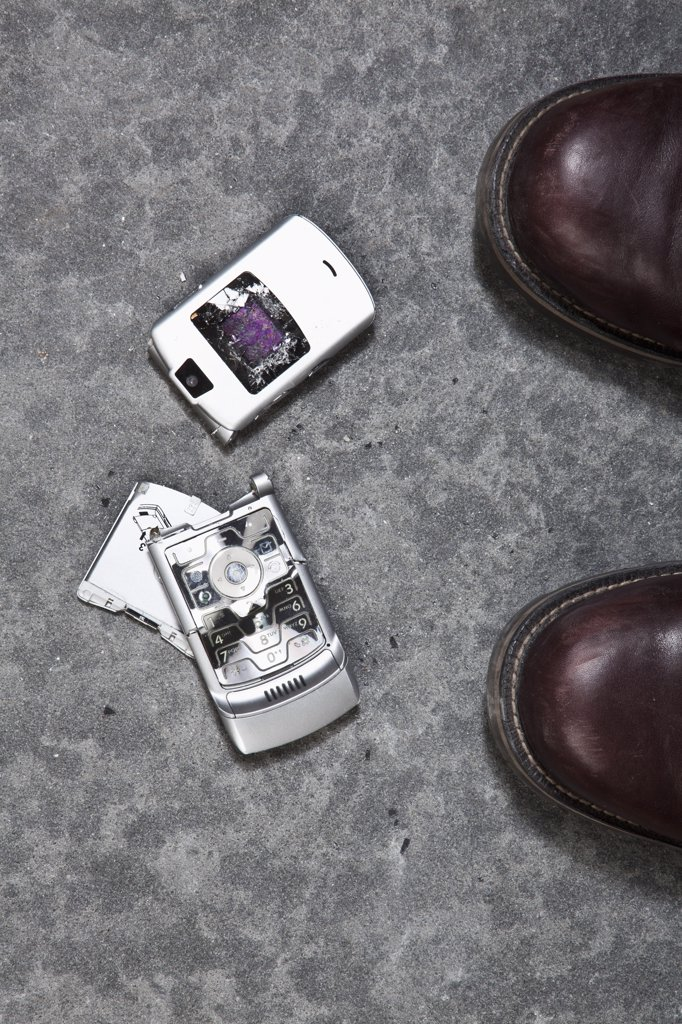 Stock Photo: 1570R-136377 Two booted feet next to a smashed mobile phone