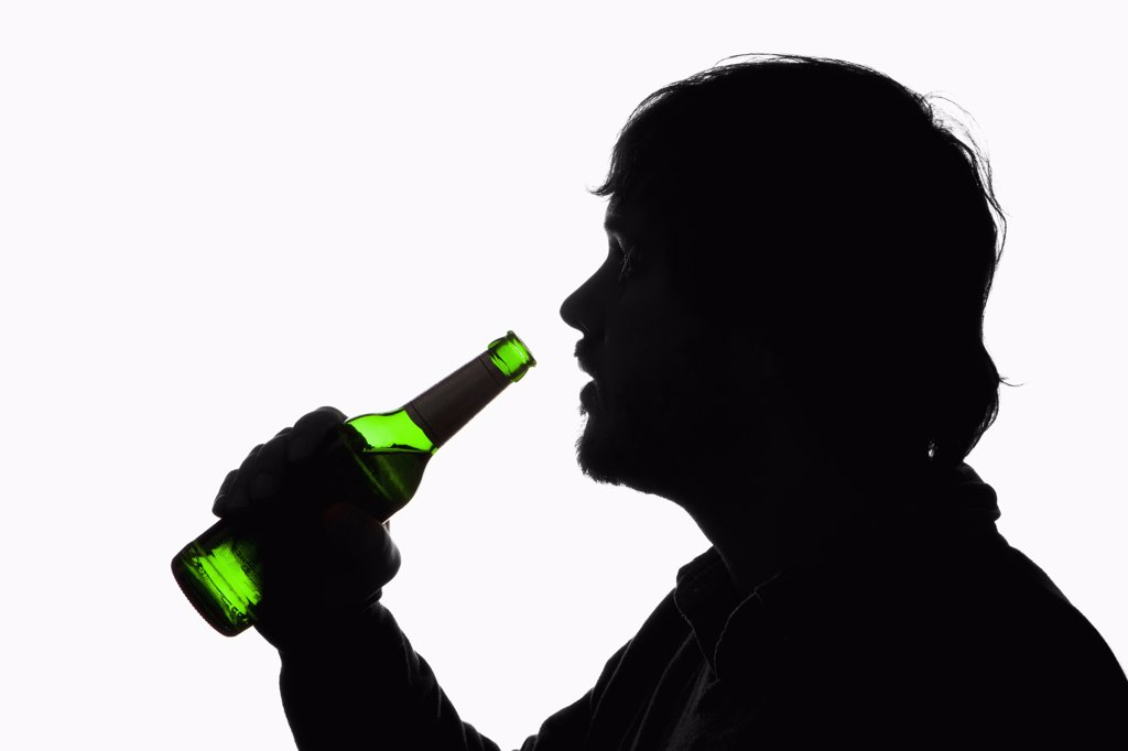 A silhouetted man about to drink from a beer bottle : Stock Photo