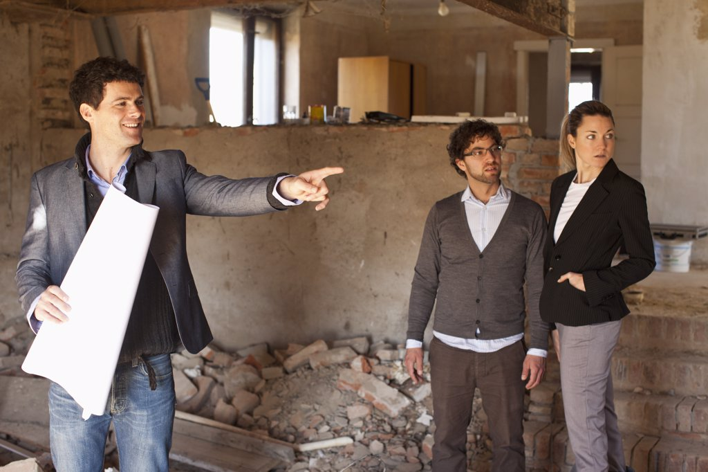 An architect showing a couple around a building site : Stock Photo