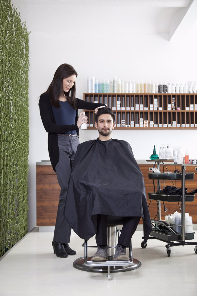 A hairdresser spraying product into a customer's hair : Stock Photo