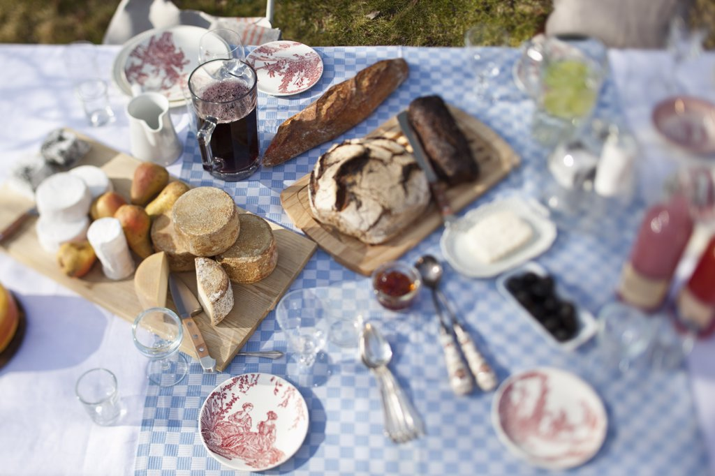 cheese wheels, bread and a lot of crockery on a dining table outside : Stock Photo