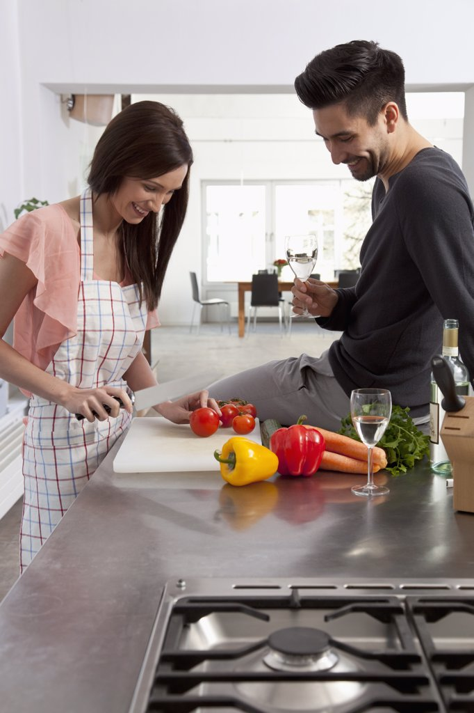 A young couple enjoying cooking together : Stock Photo