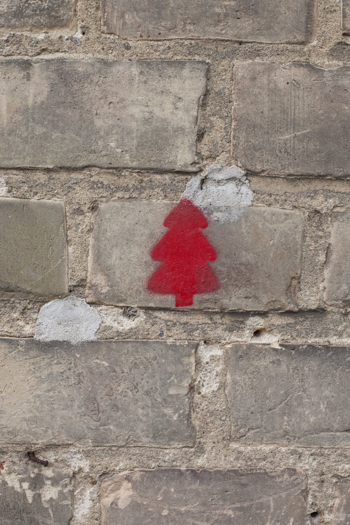 Stock Photo: 1570R-136993 A red Christmas tree stenciled on a brick wall