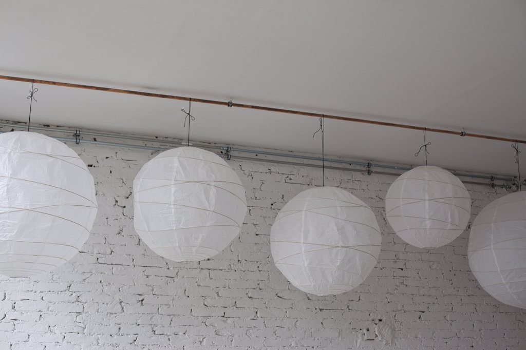 Five white round paper lanterns hanging in a row : Stock Photo