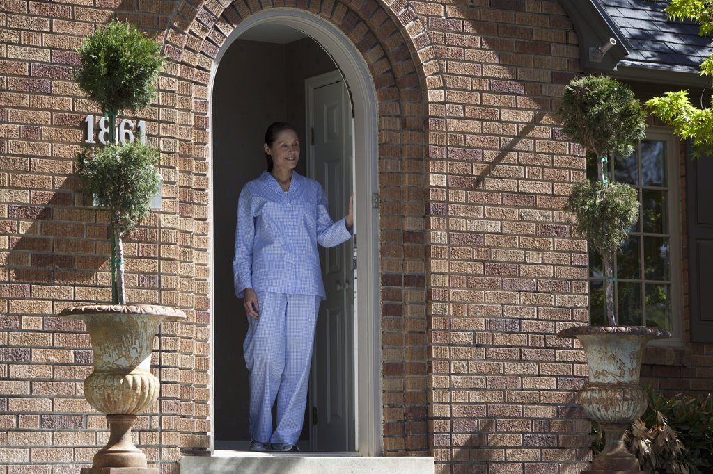 Stock Photo: 1570R-137341 Smiling woman wearing Pajamas leans on front door and looks out