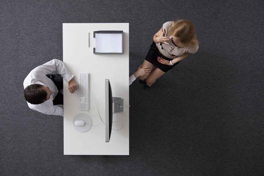 A businessman reaching under a desk to touch a woman's knee, overhead view : Stock Photo