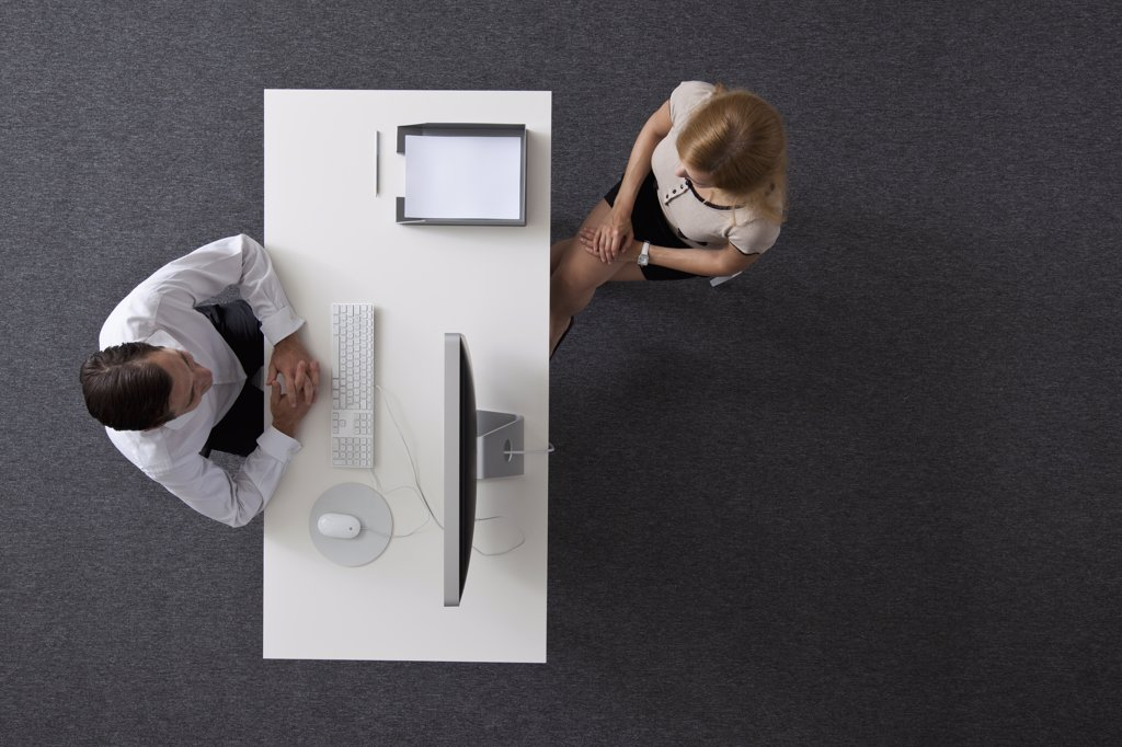 Stock Photo: 1570R-137402 A businessman and businesswoman sitting across a desk from each other, overhead view