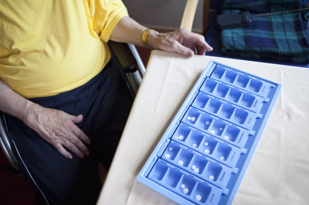 A senior man sitting next to a weekly pill organizer, focus on object : Stock Photo