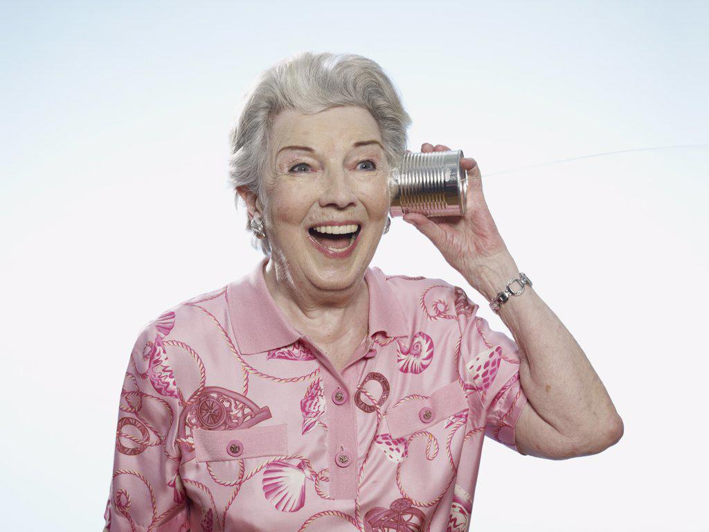 Senior woman comically listens to tin can phone : Stock Photo