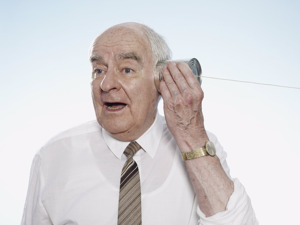 Senior man listening on tin can phone : Stock Photo
