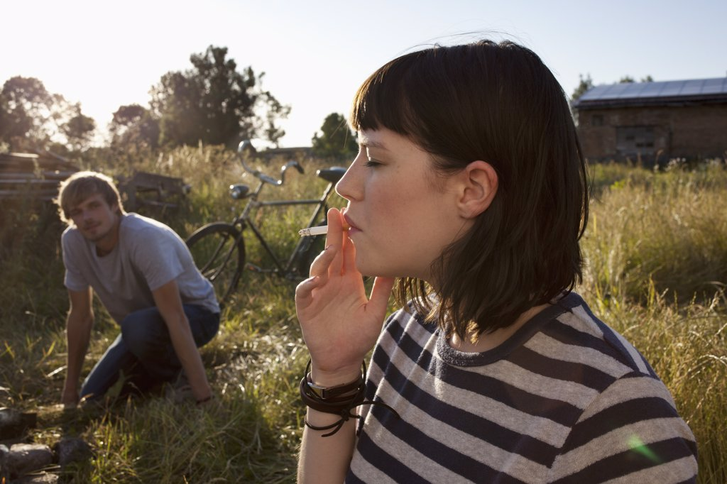 Girl smoking in field as guy in background watches : Stock Photo