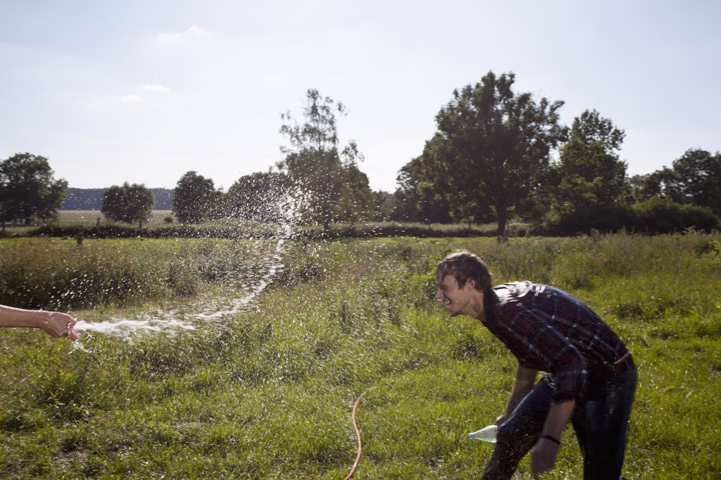 Stock Photo: 1570R-137668 Guy ducks for cover as he gets sprayed with hose