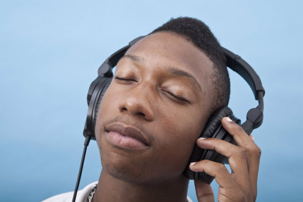 A young man listening to music with headphones, eyes closed : Stock Photo