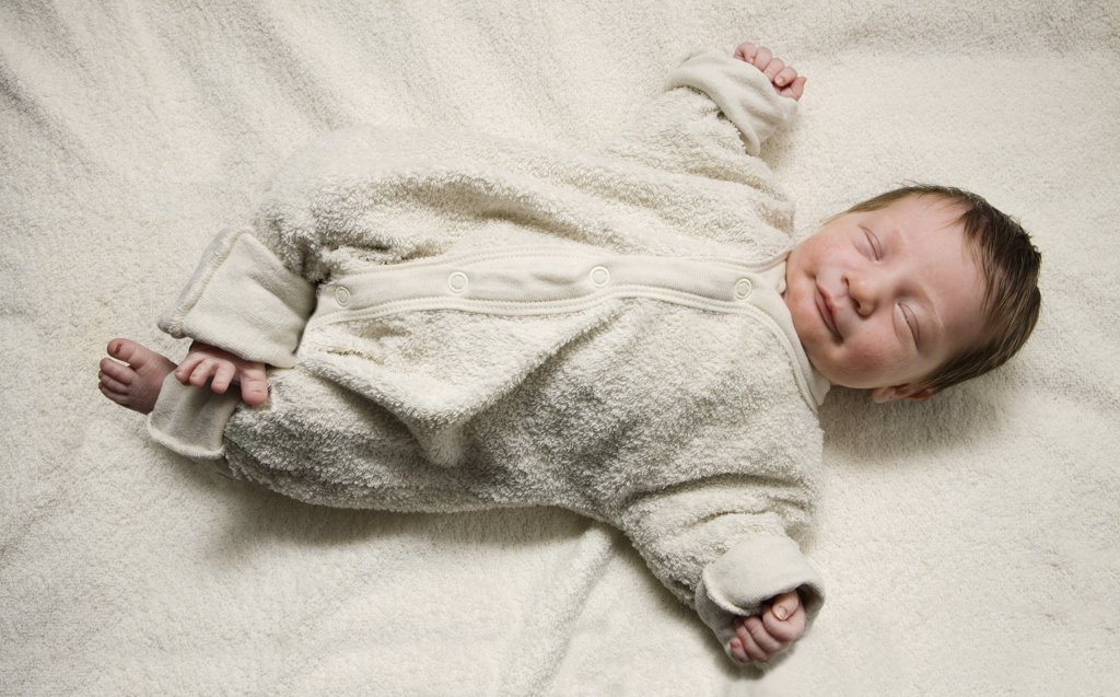 A sleeping newborn with her arms stretched out : Stock Photo