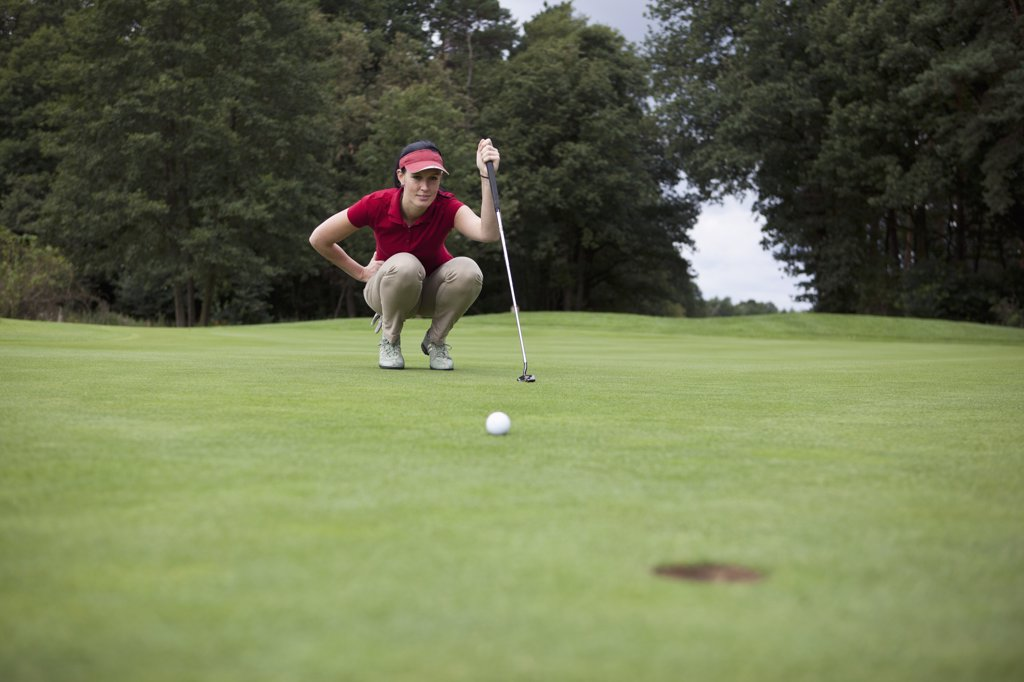 A female golfer crouching down studying the distance to the hole : Stock Photo