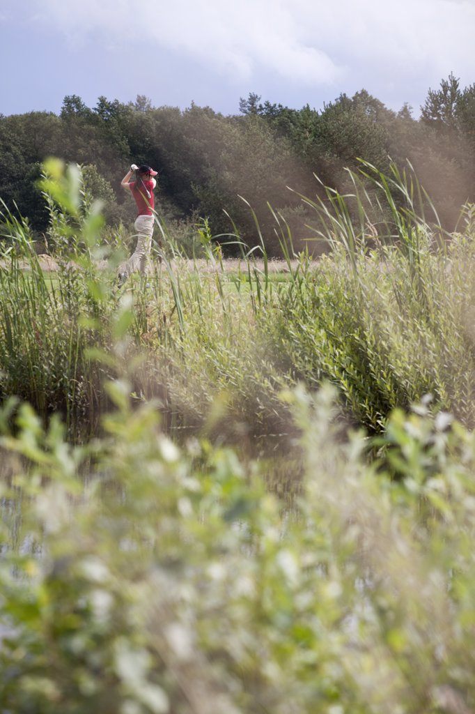 A female golfer teeing off, focus on background : Stock Photo