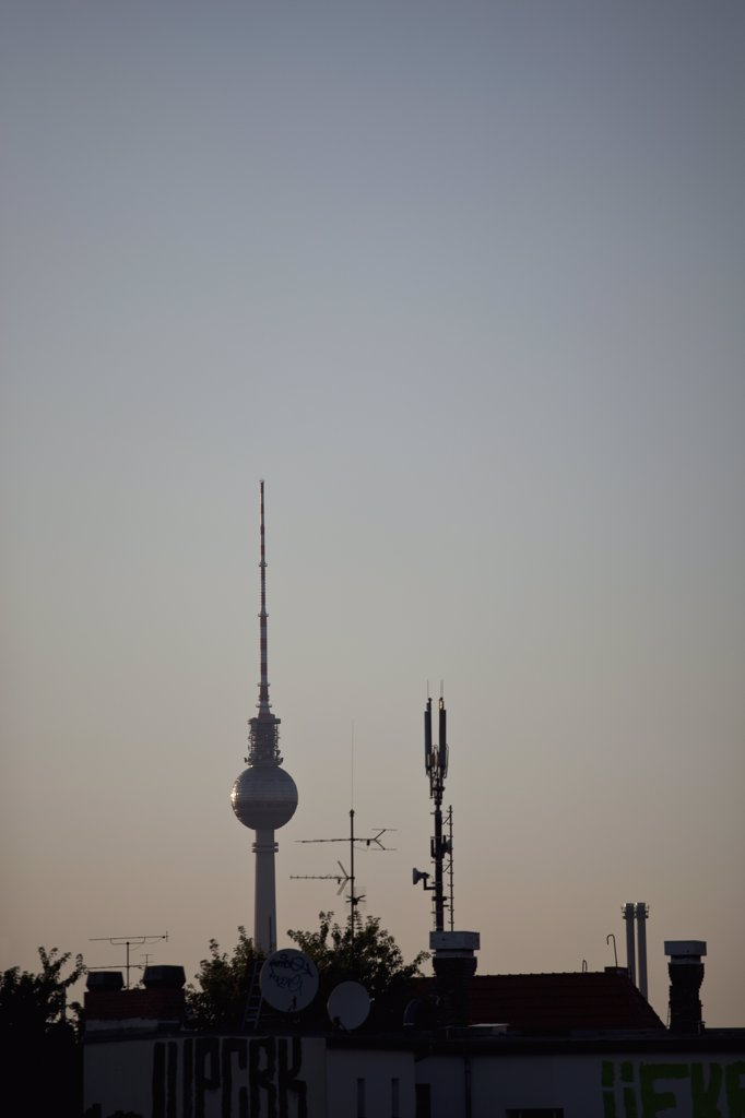 The TV Tower at Alexanderplatz behind a roof with antennas : Stock Photo
