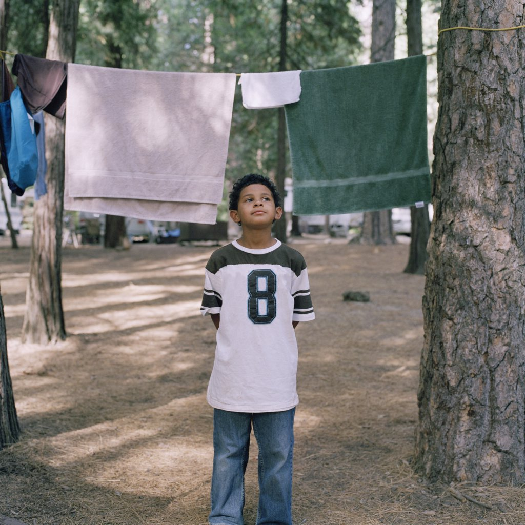 A young boy standing in front of towels on a clothesline : Stock Photo
