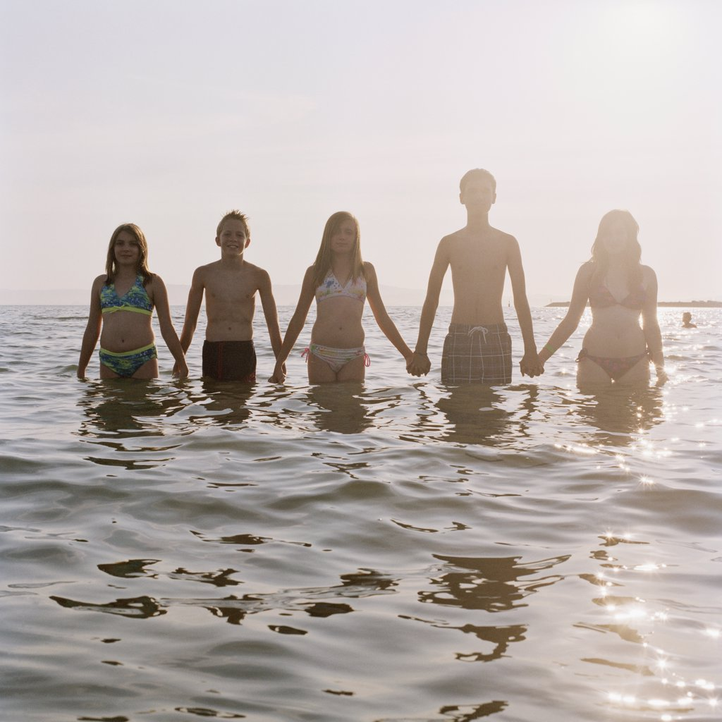 Five friends holding hands in a row while wading in the sea : Stock Photo