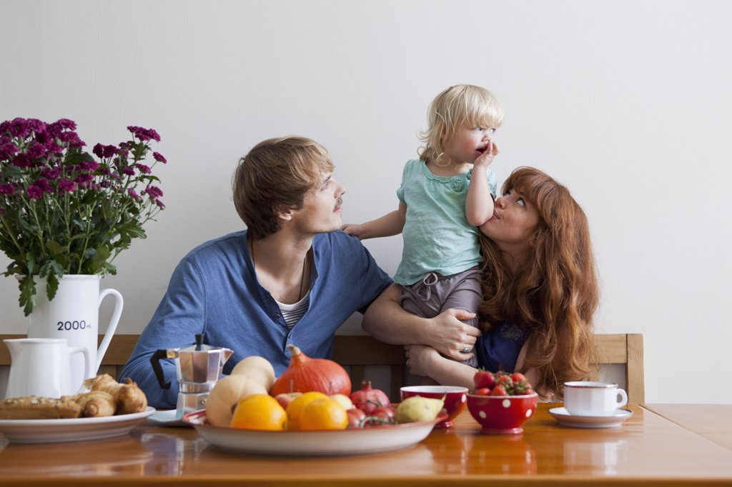 A young family having breakfast : Stock Photo