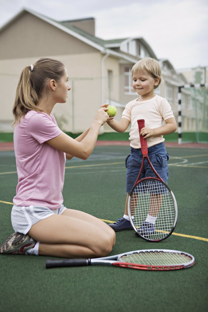 A mother teaching her young son tennis : Stock Photo