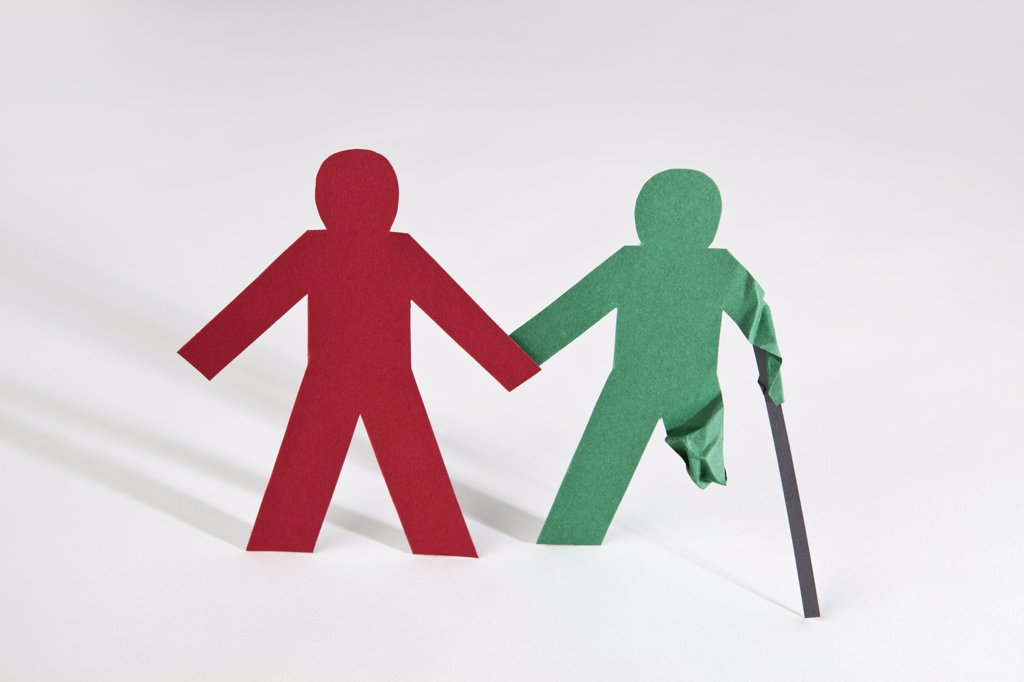 Two paper dolls holding hands, one with an injury : Stock Photo