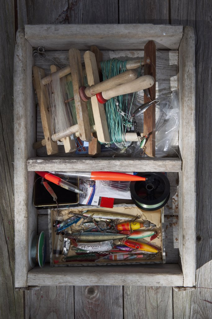 Box of fishing equipment on a background of wood panels : Stock Photo