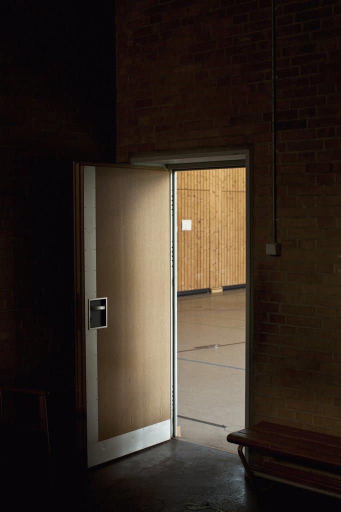 Stock Photo: 1570R-138658 Dark room with door open revealing gym