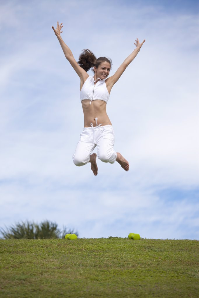 Girl jumping in mid-air in field : Stock Photo