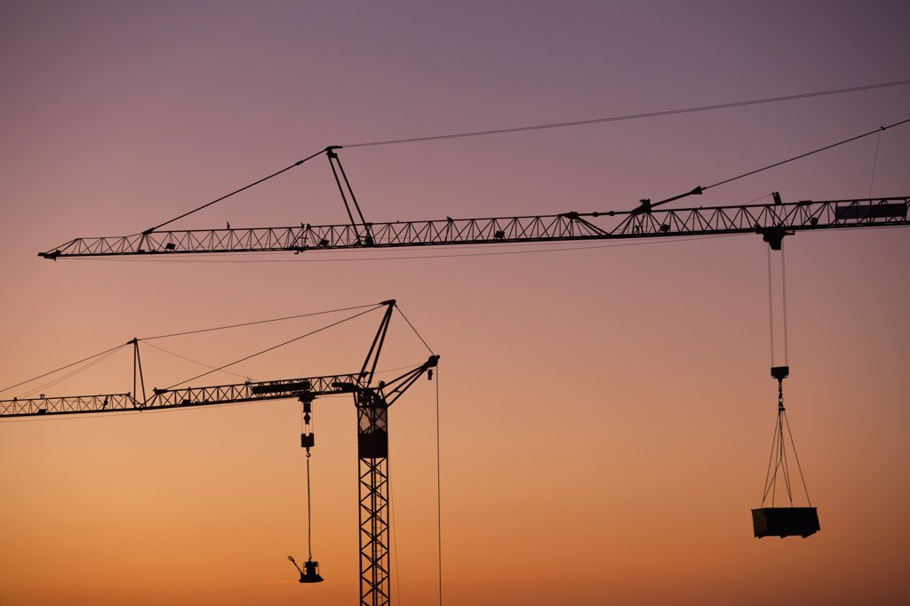 Stock Photo: 1570R-139197 Two construction cranes silhouetted against a sunset sky