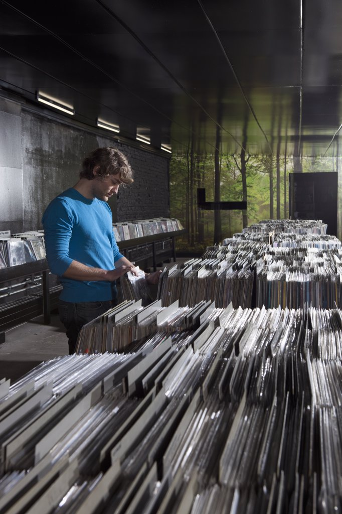 Stock Photo: 1570R-139252 A young man searching through records in a record store