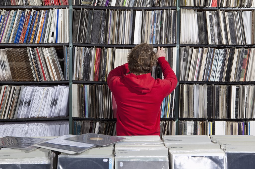 A young man selecting a record from a shelf in a record store : Stock Photo