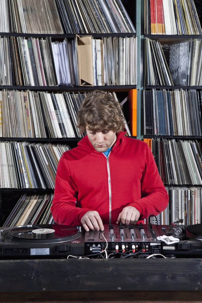 Stock Photo: 1570R-139269 A young man using decks and a sound mixer at a record store