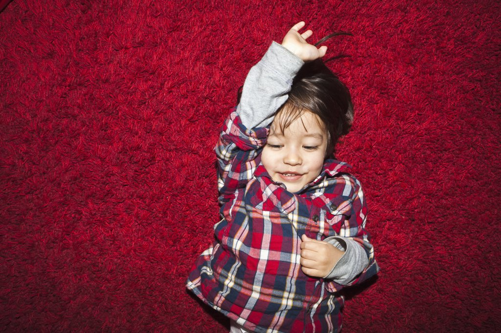 Stock Photo: 1570R-139354 A young smiling boy lying on a red carpet
