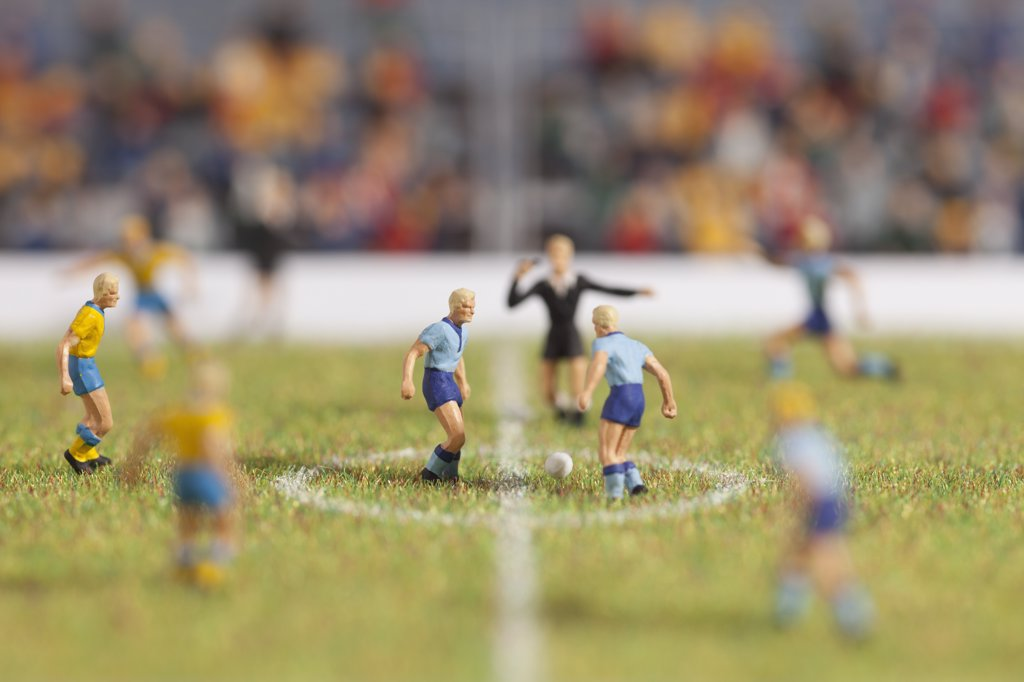 Stock Photo: 1570R-139686 Miniature soccer player figurines at the kick-off of a soccer match