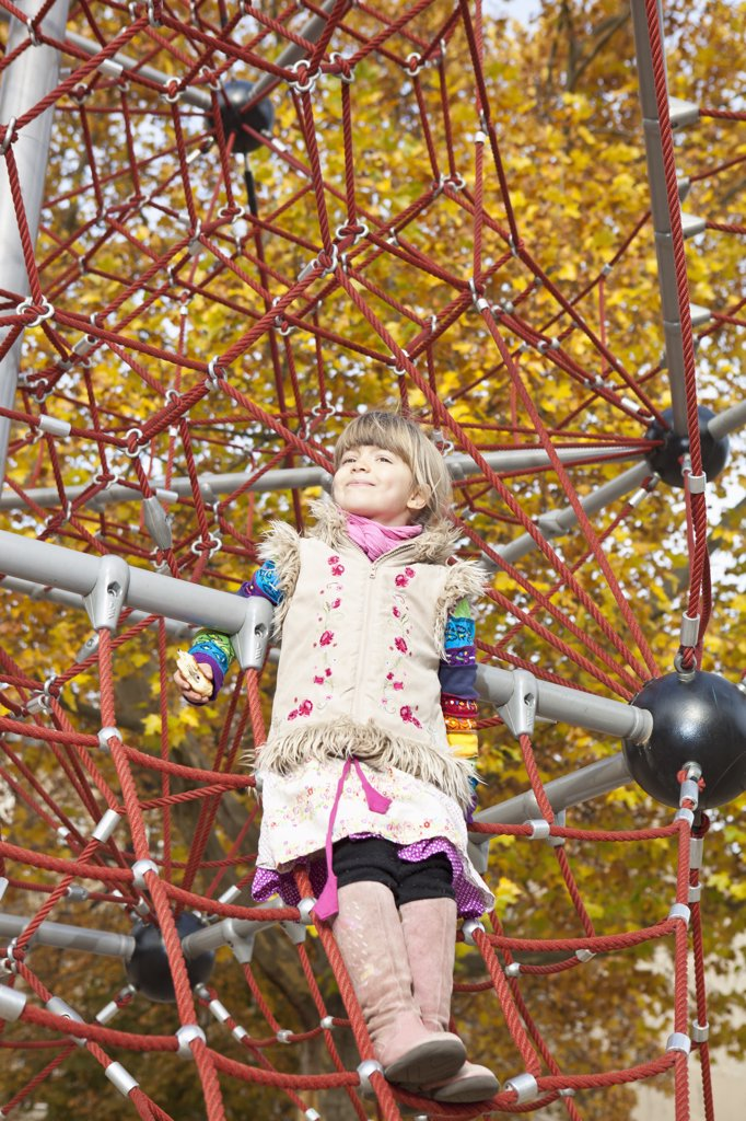 Stock Photo: 1570R-139790 Girl standing on jungle gym