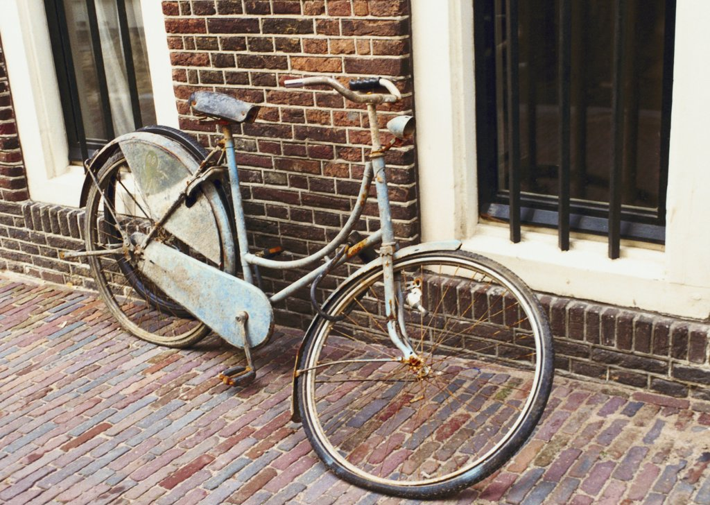 Stock Photo: 1570R-14008 rusted bicycle with broken wheel leaning against a building