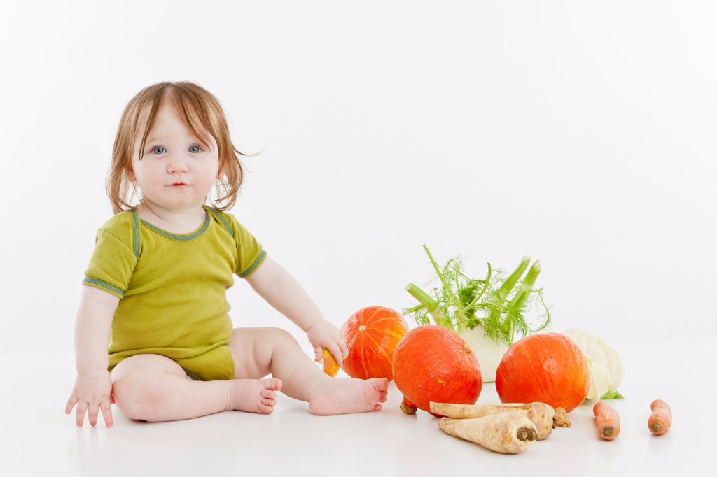 A baby girl sitting with vegetables : Stock Photo