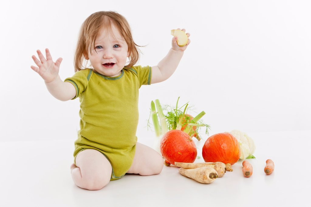 A baby girl with vegetables : Stock Photo