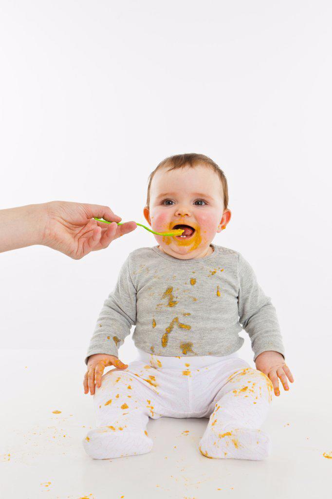 Stock Photo: 1570R-140182 An adult feeding a baby